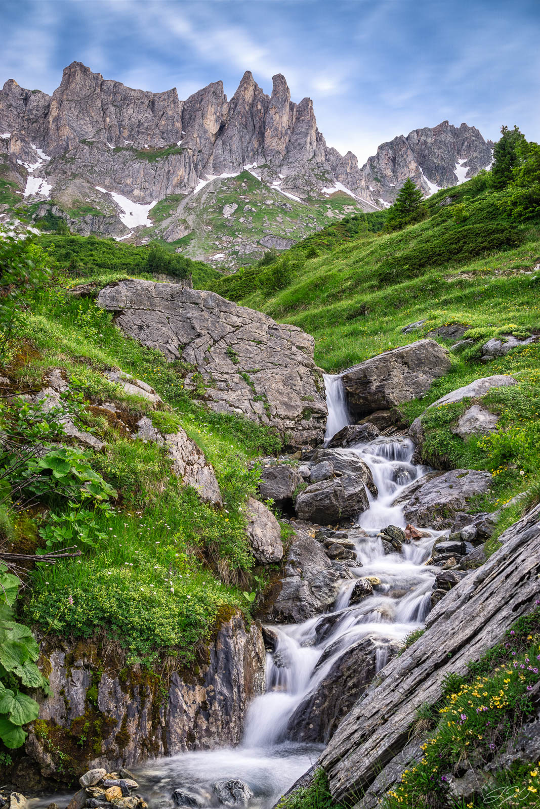 Fine Art Limited Edition of 100. An unnamed waterfall surrounded by wildflowers crashes beneath towering peaks in the French...